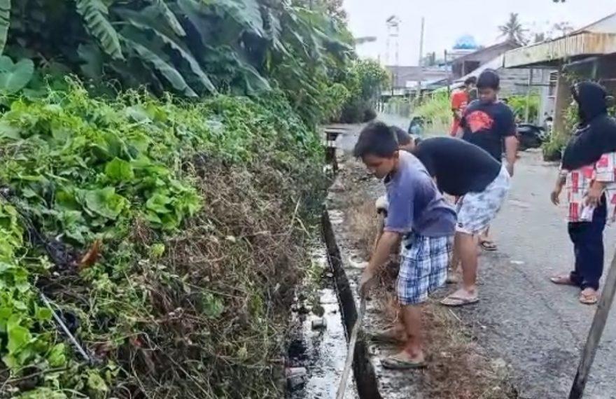 belasan pemuda bergotong royong membersihkan selokan