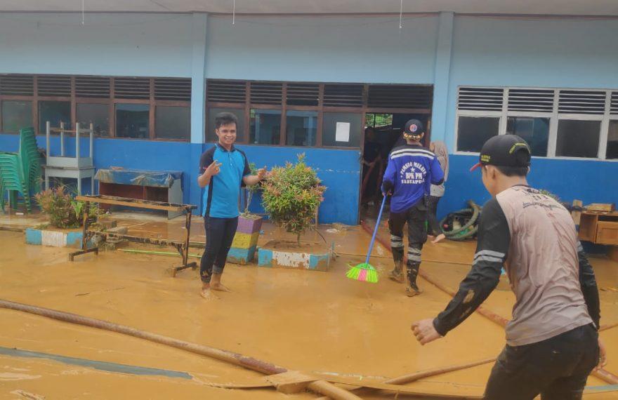 puluhan anggota Buser 690 Banjar bahu membahu membersihkan lingkungan Madrasah
