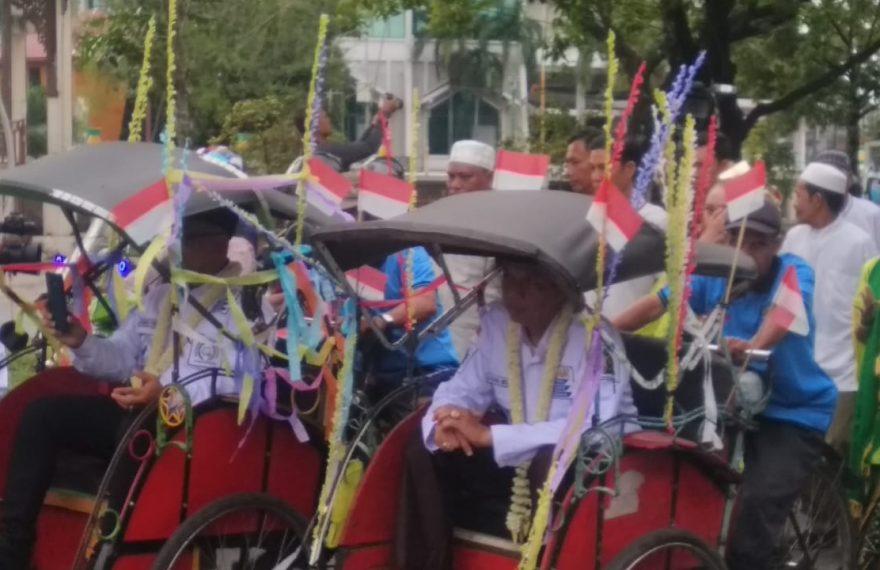Anang Misran dan Ahmad Firdaus menyapa warga dengan menaiki becak