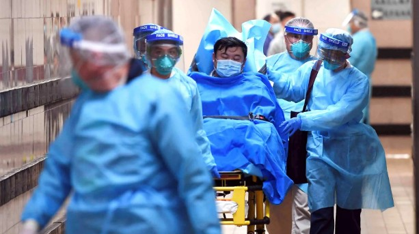 Medical staffers transport a patient with a highly suspected case of the new coronavirus at the Queen Elizabeth Hospital in Hong Kong on Jan. 22. A spike in deaths in mainland China reported Jan. 25. © Reuters