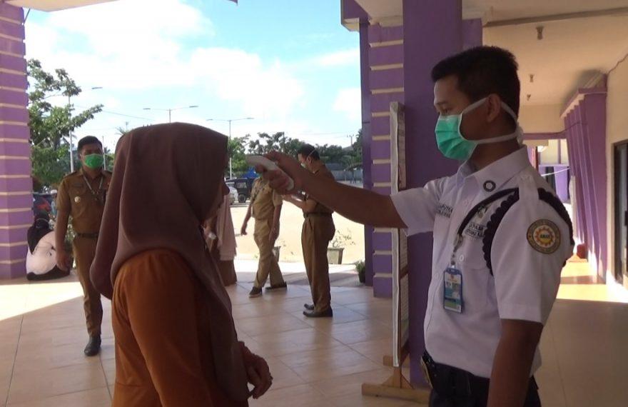 Foto : Petugas memeriksa suhu tubuh kepada warga