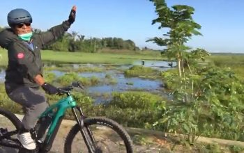 Paman Birin bersepeda di persawahan