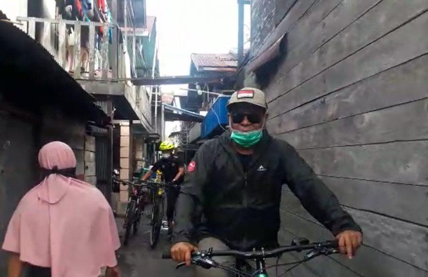 Paman Birin bersepeda menyusuri gang kecil