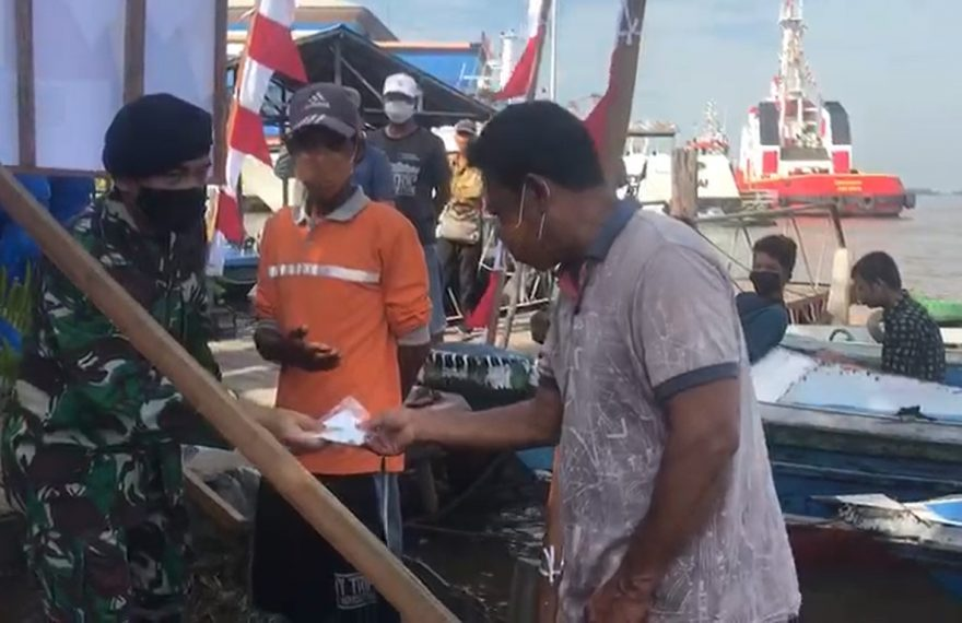 TNI AL memberikan masker kepada supir kelotok dan nelayan